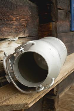 Empty Milk Can on Wooden Bench in Front of Alpine Chalet by Eising Studio - Food Photo and Video