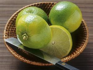 Limes, Two Whole and One Halved in a Small Basket by Eising Studio - Food Photo and Video