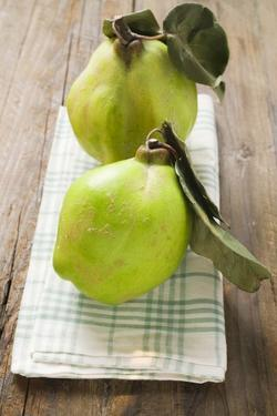 Two Quinces with Leaves on Tea Towel by Eising Studio - Food Photo and Video
