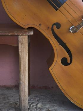 A Counterbass Leaning Against a Wooden Table, Trinidad, Sancti Spiritus Province, West Indies by Eitan Simanor