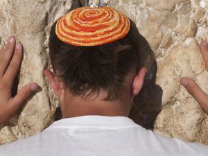 Close Up of Young Man with Bright Yarmulka Praying at Western Wall, Old City, Jerusalem, Israel by Eitan Simanor