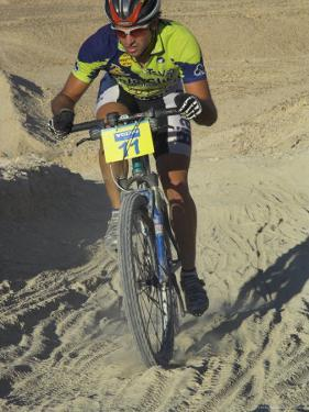 Competitior Riding Uphill on Sandy Track in Mount Sodom International Mountain Bike Race, Israel by Eitan Simanor