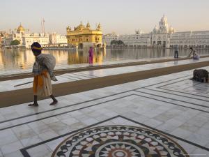Elderly Sikh Pilgrim with Bundle and Stick Walking Around Holy Pool, Amritsar, India by Eitan Simanor