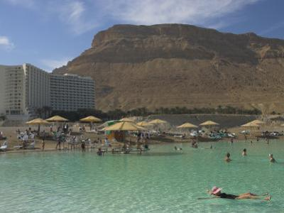 People Floating in the Sea and Hyatt Hotel and Desert Cliffs in Background, Dead Sea, Middle East by Eitan Simanor