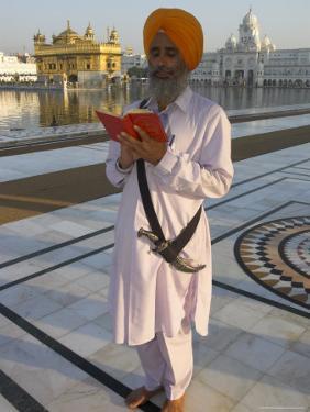 Sikh Pilgrim with Orange Turban, White Dress and Dagger, Reading Prayer Book, Amritsar by Eitan Simanor