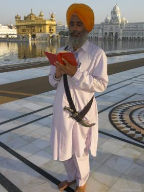 Sikh Pilgrim with Orange Turban, White Dress and Dagger, Reading Prayer Book, Amritsar by Eitan Simanor
