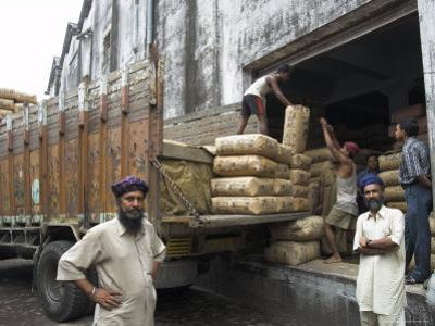 Truck Drivers in Front of Tea Sacks Being Unloaded at Kolkata Port by Eitan Simanor