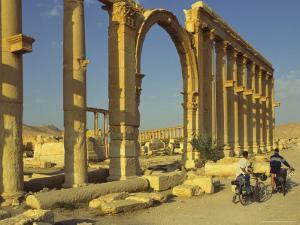 Two Cyclists Pass the Great Colonnade (Cardo), Palmyra, Unesco World Heritage Site, Syria by Eitan Simanor