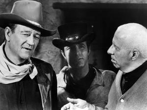 EL DORADO, 1967 directed by HOWARD HAWKS On the set, Howard Hawks with John Wayne and James Caan (b
