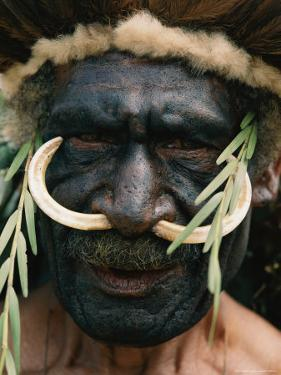Elaborate Headdress and Boar Tusks Decorate the Face of a Tribesman