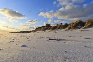 Fresh Spring Snow at Dawn Highlight Ripples and Marks in the Sand Beneath Bamburgh Castle by Eleanor