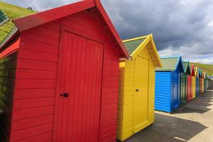 Row of Colourful Beach Huts and their Shadows, with Grassy Cliffs, West Cliff Beach by Eleanor Scriven