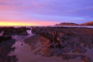 Sunrise Casts a Red Pink Hue on Rocks of a Beach Looking Towards Nugget Point by Eleanor