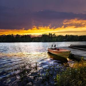 Rowboat Tied to Dock on Beautiful Lake with Dramatic Sunset by elenathewise
