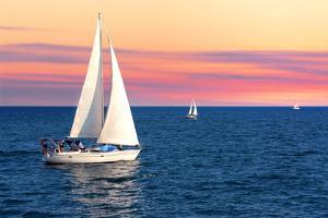 Sailboat Sailing towards Sunset on a Calm Evening by elenathewise