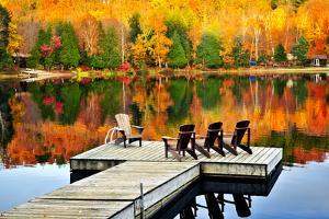 Wooden Dock with Chairs on Calm Fall Lake by elenathewise