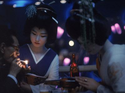 Patron of Nightclub Uruwashi Having His Cigarette Lit by Geisha