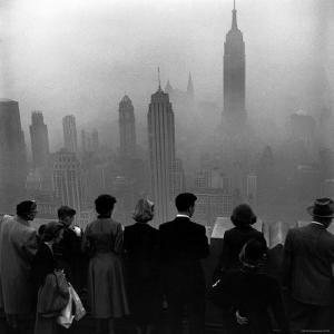 People on Top of a Building Looking Down Into Downtown Misty Smog covering Empire state Building by Eliot Elisofon