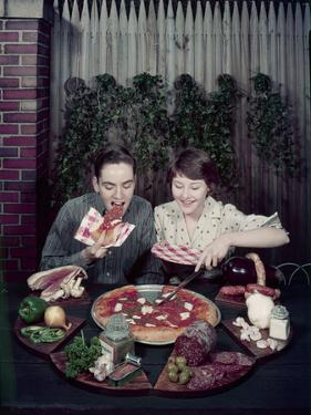 Teen Couple Eating Pizza from a Garden Table, 1960 by Eliot Elisofon
