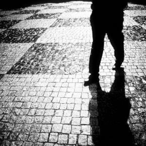 Silhouette of Mans Legs Walking on Cobblestone Street at Night by Elke Hesser