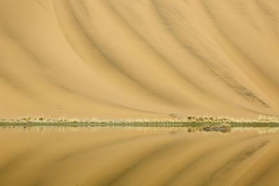 China, Inner Mongolia, Badain Jaran Desert. Dunes reflected in a lake. by Ellen Anon