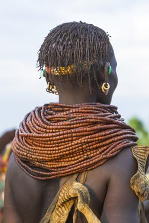 Africa, Ethiopia, Southern Omo Valley. Nyangatom woman wear heavy beads and other decorations.