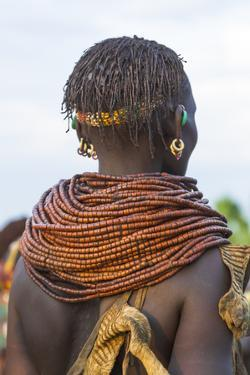 Africa, Ethiopia, Southern Omo Valley. Nyangatom woman wear heavy beads and other decorations. by Ellen Goff