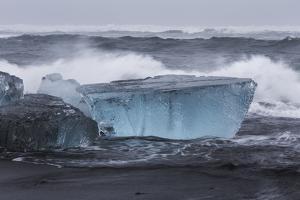 Iceland, Skaftafell National Park, Surf hits glacial ice on a black sand beach. by Ellen Goff
