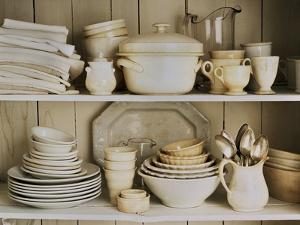 White Tableware and Table Cloths on a Kitchen Shelf by Ellen Silverman