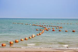 Arabian Peninsula, Persian Gulf, State of Qatar, Doha. Orange buoys in bay. by Emily Wilson