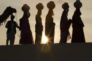 India, Manvar, Desert, Sand Dunes. Colorfully Dressed Women Walking with Pots on their Head by Emily Wilson