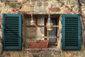 Italy, Monteriggioni. Stone wall, curtained window with blue shutters. by Emily Wilson