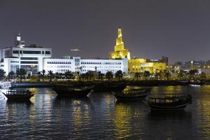 State of Qatar, Doha. Dhow harbor at night. Left: Ministry of Finance. by Emily Wilson