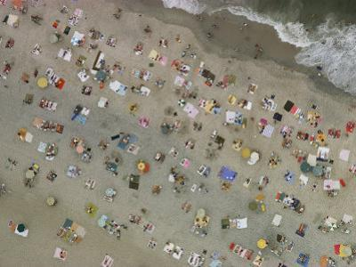 Aerial view of wall-to-wall seaside sunbathers by Emory Kristof