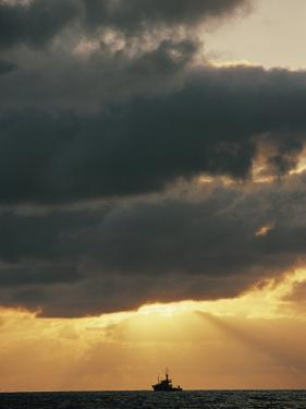 The Sun Shines Through the Clouds over the Atlantic Ocean by Emory Kristof