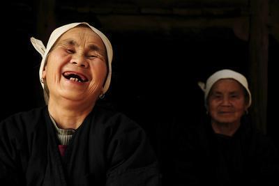 Two Dong Women, One Laughing, in a Dark Room, Sanjiang Dong Village, Guangxi, China