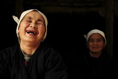 Two Dong Women, One Laughing, in a Dark Room, Sanjiang Dong Village, Guangxi, China by Enrique Lopez-Tapia