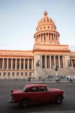 A Classic American Car Drives Past the El Capitolio Building in Downtown Havana by Eric Kruszewski