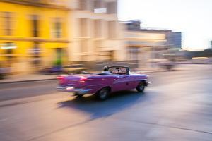 A Classic American Convertible Car Speeds Down a Street in Downtown Havana by Eric Kruszewski