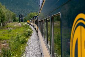 The Alaska Railroad Train Travels Through a Lush Landscape as it Approaches a Bridge by Eric Kruszewski