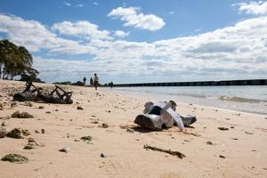 Two Pairs of Sandals Sit in the Sand as Tourists Walk the Beach Along the Ocean Water by Eric Kruszewski