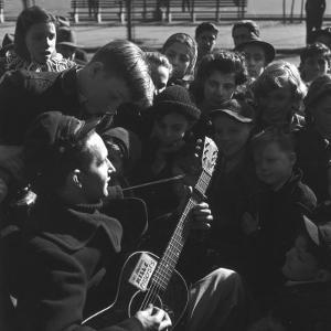 Folk Singer Woody Guthrie Playing Guitar for Group of Children by Eric Schaal