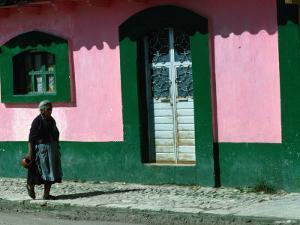 Elderly Woman Walking Past Pink and Green Building, Chiapas, Mexico by Eric Wheater