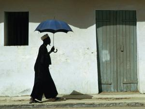 Man Walking with Umbrella, St. Louis, Senegal by Eric Wheater