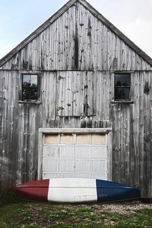 A Canoe Sits In Front Of A Weathered Old Boat House On The Coast Of Maine