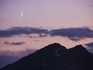 A Crescent Moon Rises over Clouds and Mountains at Twilight in Glacier Peak Wilderness, Washington. by Ethan Welty