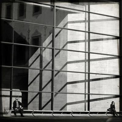 Two People Sitting Outside a Modern Glass Building