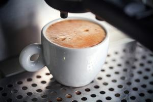 White Ceramic Cup of Fresh Espresso with Foam in the Coffee Machine. by Eugene Sergeev