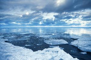 Winter Coastal Landscape with Floating Melting Ice Fragments by Eugene Sergeev