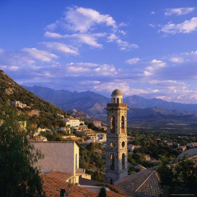 https://imgc.allpostersimages.com/img/posters/evening-view-across-rooftops-and-church-tower-to-mountains-lumio-near-calvi-corsica-france_u-L-P2QTVV0.jpg?p=0